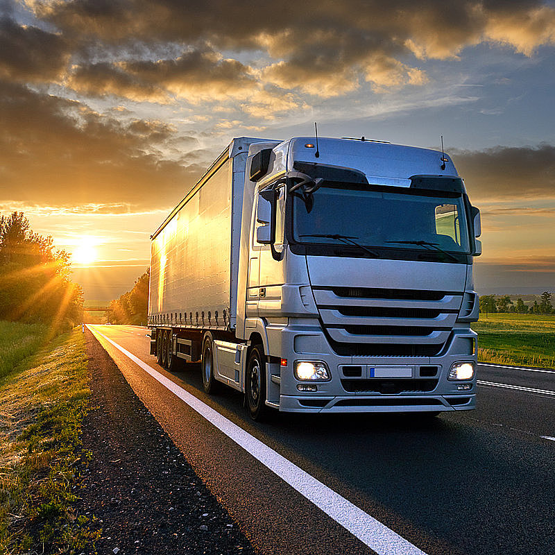 Road Transport Truck drives at sunset climate